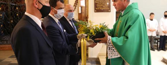 Zdjęcie przedstawia księdza i burmistrza w asyscie radnych